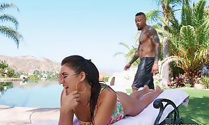 Young brunette pleasuring handsome black guy by the pool